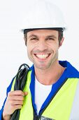 Portrait of happy electrician with wire against white background