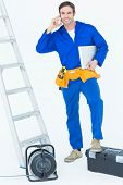 Confident electrician with leg on tool box using mobile phone over white background