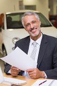 Smiling businessman looking at camera at new car showroom