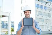 Portrait of handsome male architect showing digital tablet outdoors