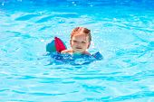Baby girl swimming in blue pool with floats sleeves at summer vacation