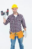 Portrait of confident male repairman holding drill machine on white background