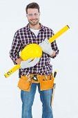 Portrait of confident handyman holding hard hat and spirit level on white background