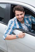 Young man smiling at camera showing key in his car