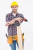 Portrait of confident male carpenter with drill machine and plank on white background