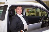 Smiling businessman using laptop in his car at new car showroom