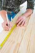 Cropped image of carpenter marking with tape measure on wooden plank against white background