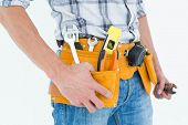 Cropped image of technician with tool belt around waist against white background