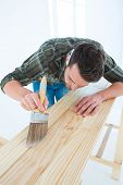 Male carpenter using brush on wooden plank at home