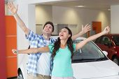 Young couple smiling and cheering at new car showroom