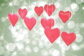 Love hearts against shimmering light design on green