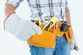 Cropped image of technician with tool belt around waist using adjustable wrench against white background