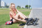 Fit blonde getting ready to roller blade on a sunny day