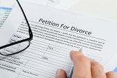 Hand With Pen On Petition For Divorce Paper