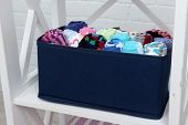Different socks in textile box on shelf and white brick wall background