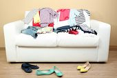 Colorful clothing on white sofa and female shoes on light wall background