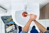 Male Plumber Using Plunger In Bathroom Sink