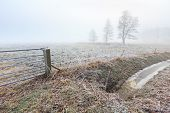 Misty Frozen Landscape Of Farmland In Winter Time