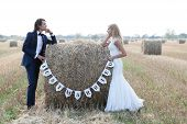 image of married couple  - Married couple standing with the elbows on a hay bale that is written  - JPG
