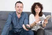Middle Aged Couple Relaxing In Sofa At Home Reading A Book