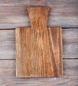 Cutting board on rustic wooden planks background