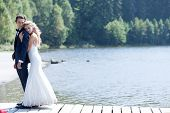 stock photo of bridge  - Romantic married couple standing on a foot bridge near a lake showing an embrace full of love - JPG