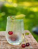 glass with drops of dew and cherries