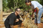 People play with indochinese baby tiger in Saiyok, Thailand.