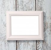 Photo frame on color wooden background