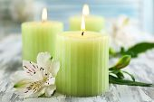 Beautiful candles with flowers on wooden background
