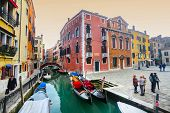 Gondolas Moored Along Water Canal In Venice