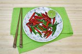 Decorative Composition With Chili Pepper And Lime On A Plate And Chopsticks.