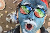 foto of crazy face  - blue face crazy rainbow glasses man singing - JPG