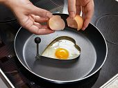 Woman Preparing Fried Eggs In Heart Form
