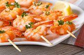 stock photo of braai  - Delicious fried shrimp on wooden skewers close - JPG