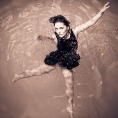 Woman Floating On Swimming Pool In Black Dress.