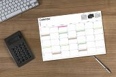 Calendar And Calculator On Wooden Table