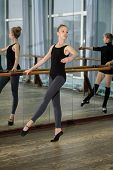 stock photo of ballet barre  - Girls exercising at the barre during ballet class and reflecting in the mirror