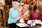 Senior woman and granddaughter laughing having fun with coffee and cake in cafe