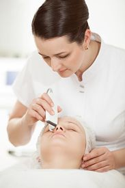 foto of ultrasonic  - Professional beautician providing ultrasonic facial cleaning at beauty treatment salon - JPG