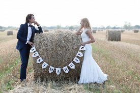 stock photo of married  - Married couple standing with the elbows on a hay bale that is written  - JPG