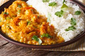 picture of shrimp  - Shrimps in curry sauce with rice and cilantro closeup on a plate - JPG