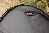 pic of tent  - Young woman looks out of tent during a rain - JPG