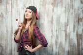 image of lollipops  - Waist up portrait of cute hipster girl with lollipop and cap - JPG
