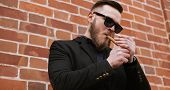 image of cigar  - Side bottom view of handsome bearded man smoking a cigar over brick wall - JPG