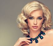 stock photo of precious stones  - Beautiful cute girl with blonde curly hair with a necklace of  blue and green precious stones - JPG