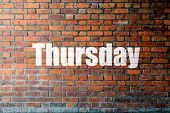 stock photo of thursday  - Red Brick wall texture background with a word Thursday - JPG