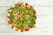 image of italian parsley  - Italian pasta fusilli with fresh garlic and rocket leaves spanish chorizo parsley parmesan cheese on gingham plate white wood background - JPG