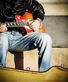 foto of guitarists  - close up of a guitarist playing in the street in vintage effect - JPG