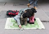 stock photo of begging  - A young man is begging on the ground of a main street in Budapest Hungary - JPG